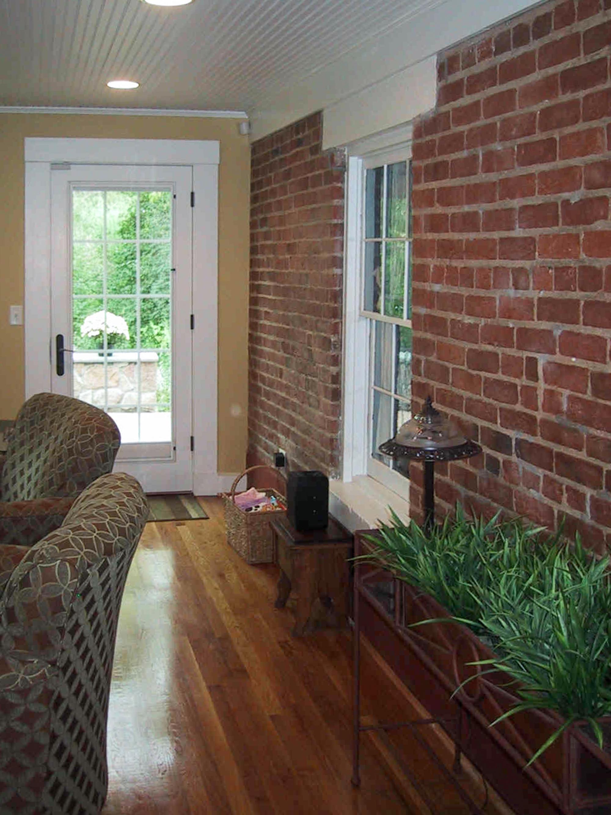 sunroom interior with exposed brick wall Wilcox Architecture