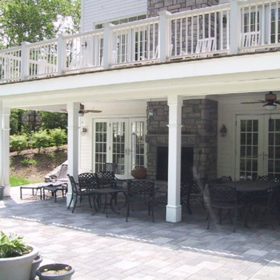 covered paved patio with new deck over a stone fireplace