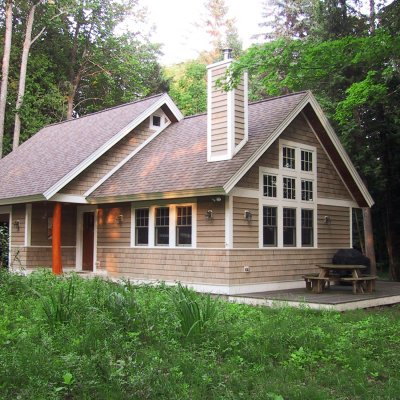 Cottage exterior on wooded lakefront lot