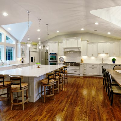 Giant white gourmet kitchen with wood floors