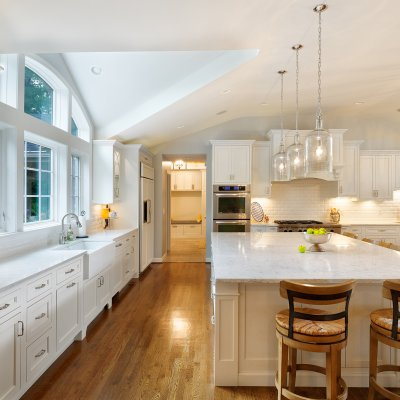Long kitchen counter with dormer ceiling and large arched windows
