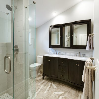 Bathroom with glass shower, black vanity, and mirror sloped ceiling