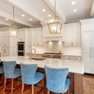 kitchen with white cabinets, white backsplash, and large island